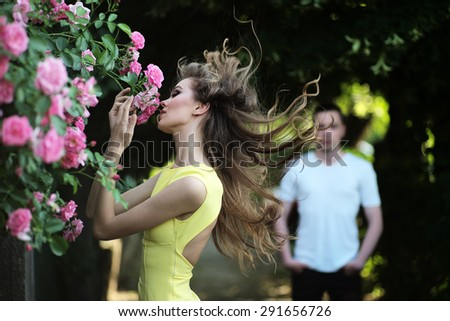 Sexual young blonde woman with bright makeup and curly hair in yellow dress smelling lush bush of pink rose and man in background, horizontal picture - stock photo