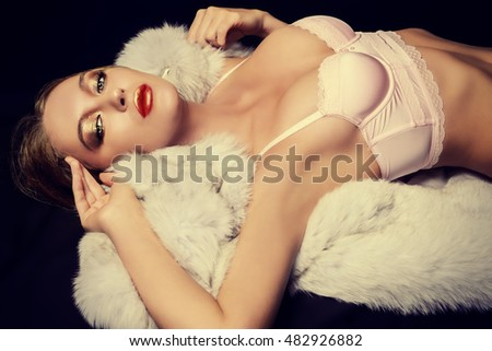 Sexual young woman in a beautiful pink lingerie lying on a white fur over black background.