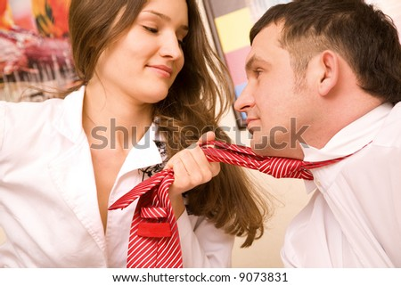 Sexual young woman in formal suit holding in fist tie of her colleague