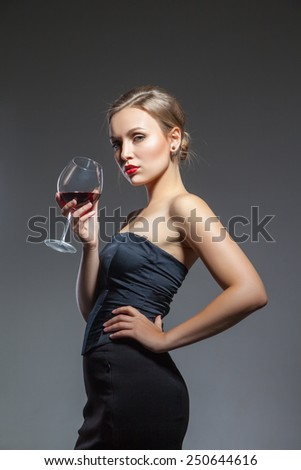 Sexual young woman posing in black dress with wine glass in hand, isolated, over the gray background.  - stock photo