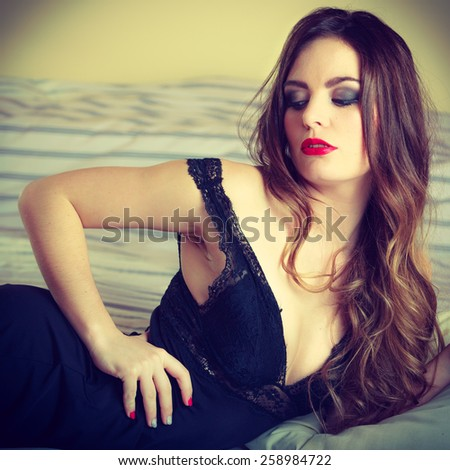 Sexuality and temtation of women. Attractive seductive long curly hair woman in black lingerie on bed. Indoor.