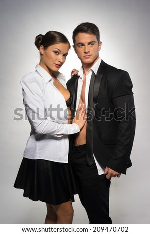 Sexually Attractive Couple in Open Black and White Corporate Attire, Isolated on Gray Background.