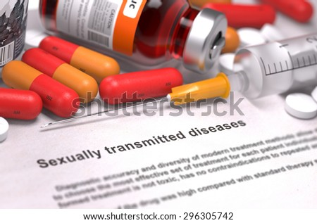 Sexually Transmitted Diseases - Printed Diagnosis with Red Pills, Injections and Syringe. Medical Concept with Selective Focus. - stock photo