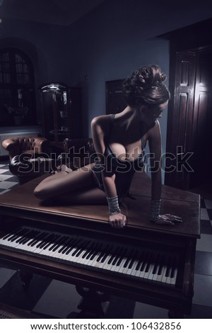 Sexy actress laying on a piano - stock photo