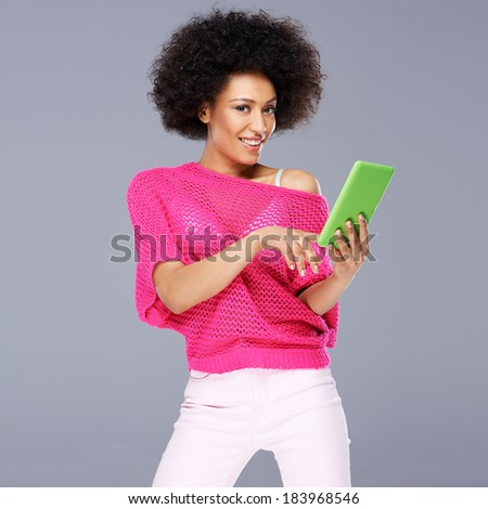 Sexy African American woman in a fashionable trendy pink blouse standing smiling with a tablet in her hands on a grey background