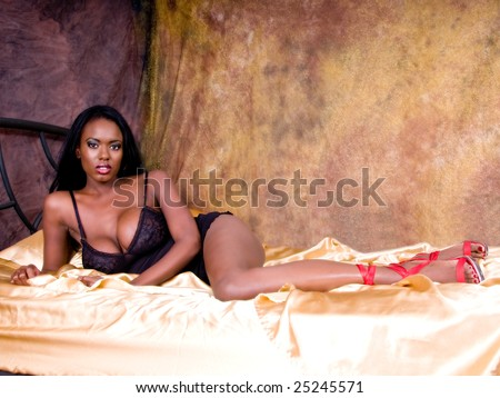 Sexy African American woman with very large breasts looking lovely in black lingerie  in a gold bedroom - stock photo