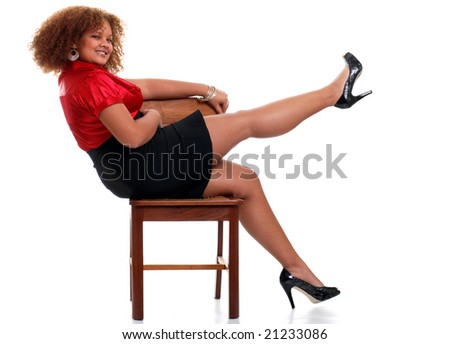 sexy african woman on a chair lifting her leg - stock photo