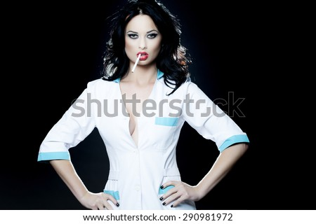 Sexy alluring young brunette nurse in white uniform smoking standing on black background, horizontal picture - stock photo