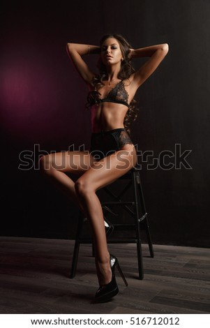Sexy and beautiful young woman with dark wavy hair, long legs and bronzed skin is posing in the black lacy underwear in the studio on the chair, dark background