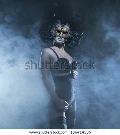 Sexy and bizarre woman in mask and lingerie over the smoky background - stock photo