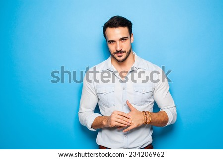 sexy and confident handsome man on a blue background - stock photo