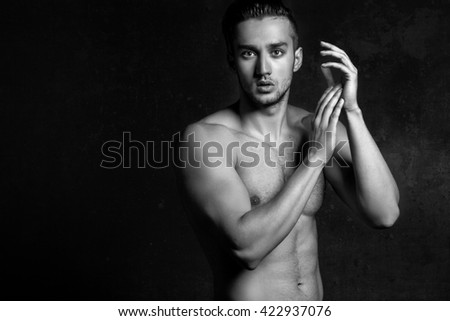 Sexy and expressive shirtless male model flirting against black background - stock photo