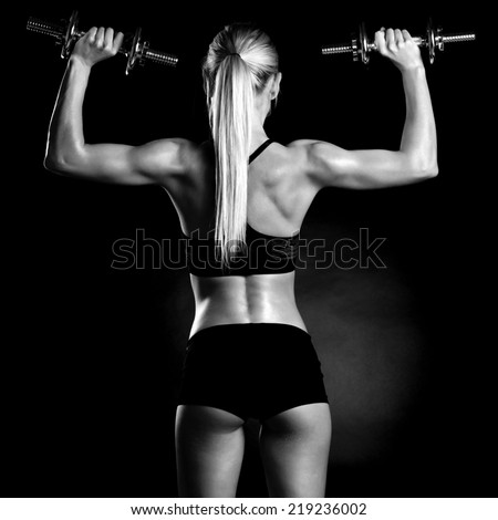 Sexy and fit woman lifting hand weights - stock photo