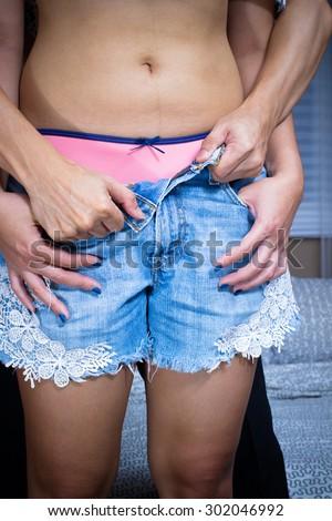 Sexy asian couple, male unbutton female blue jeans - stock photo