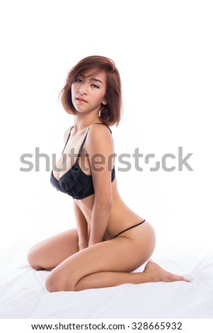 Sexy asian girl wearing lingerie and thong sitting on the bed