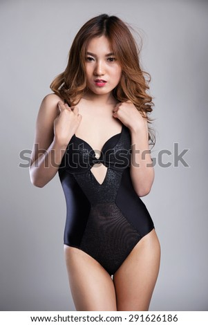 Sexy asian woman in lingerie, black one piece, posing in studio - stock photo