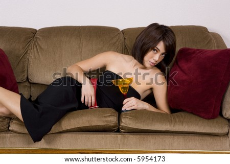 Sexy Asian woman lying on couch with drink glass - stock photo