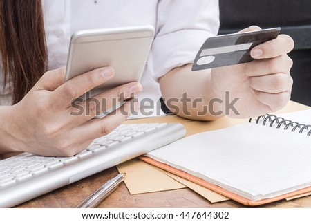 Sexy Asian woman using computer to online shopping and pay by credit card, Low light, selective focus on hand, can be used for e-commerce, business, technology and internet concept - stock photo