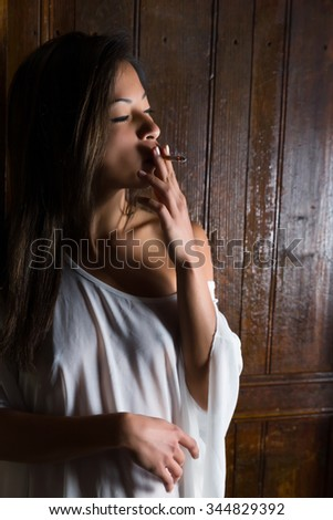 Sexy Asian young woman in lingerie smoking a cigarette standing in a door
