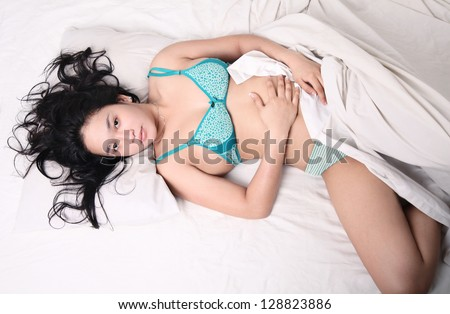 sexy asian young woman sleeping on bed high angle - stock photo