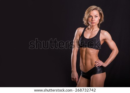 Sexy athletic blonde posing on a black background. Muscular girl on a black background. Fitness woman, a beautiful healthy woman. - stock photo