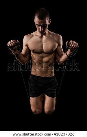 Sexy Athletic Man showing six pack abs. Isolated on black background with copy space