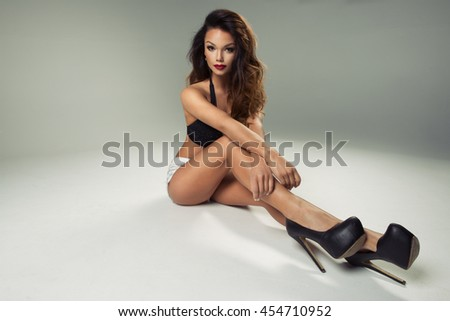 Sexy attractive brunette woman posing in swimwear and jeans in studio  - stock photo