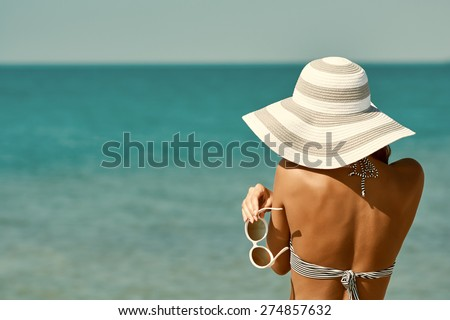 Sexy back of a beautiful woman in bikini, creative hat and sunglasses on sea background. Retro vintage toned image, film simulation. - stock photo