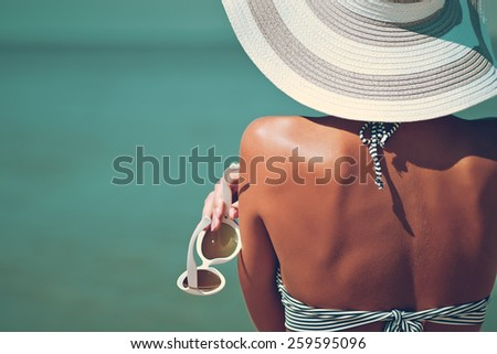 Sexy back of a beautiful woman in striped bikini and hat with creative white sunglasses. Retro toned image. - stock photo