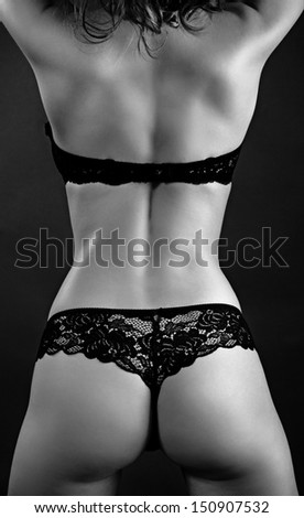Sexy back of young beautiful blonde in lingerie over dark background.