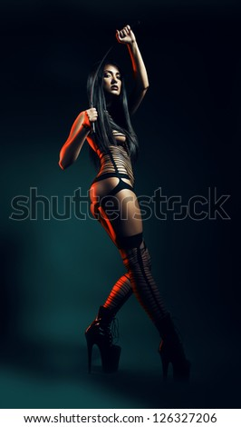 sexy bdsm woman in red light with whip - stock photo
