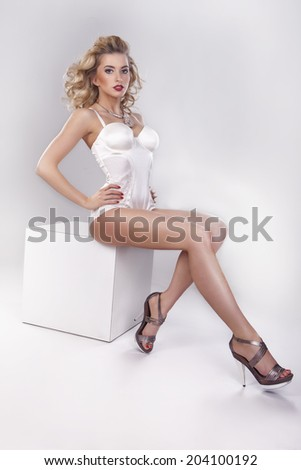 Sexy, beautiful blonde girl is sitting on the white cube - stock photo