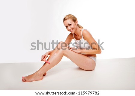 Sexy beautiful blonde woman in a vest sitting on the floor woman waxing her long slender shapely legs in a beauty concept - stock photo