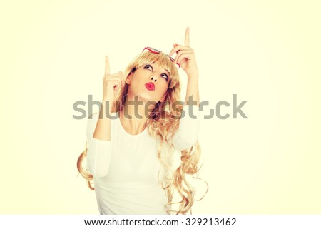 Sexy beautiful blonde woman in sunglasses pointing up. - stock photo