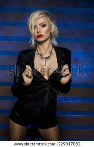 Sexy beautiful blonde woman posing in lack leather clothes. Girl with perfect slim body.  - stock photo