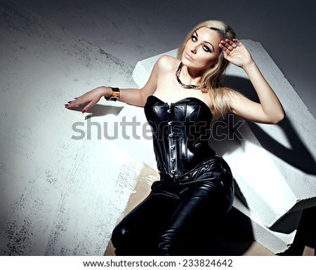 Sexy beautiful blonde woman posing in leather costume, looking at camera. Sensual photo. - stock photo