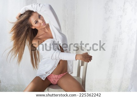 Sexy beautiful blonde woman with perfect body sitting on chair, posing - stock photo