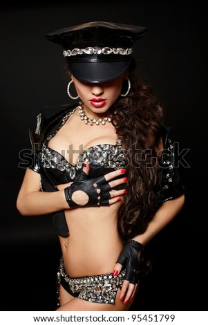 sexy beautiful  brunette semi nude police woman with long curly hair with handcuffs  with bright makeup and red lips isolated on black - stock photo