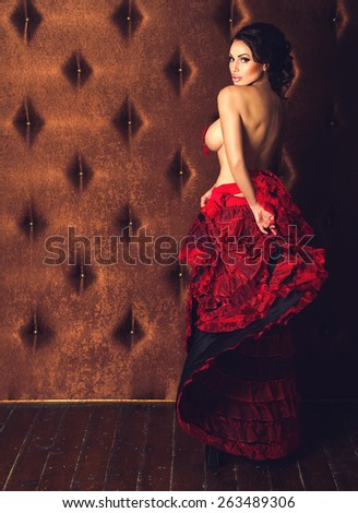 Sexy beautiful brunette woman dancing striptease in red skirt with naked breasts on a luxury velvet background with copyspace - stock photo