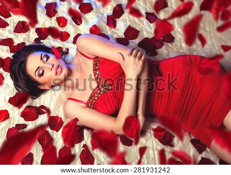 Sexy beautiful brunette woman in red dress laying on a bed under romantic falling rose petals  - stock photo