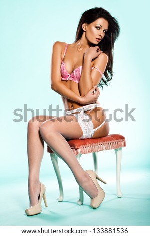 Sexy beautiful brunette woman posing obliquely on a stool in lingerie with her head turned over her shoulder glancing sideways at the camera, studio portrait on blue - stock photo