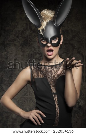 Sexy, beautiful, charming woman in black dress and carnival black rabbit mask in funny pose. - stock photo