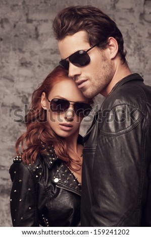 Sexy beautiful couple looking at the camera. While standing on the brick wall