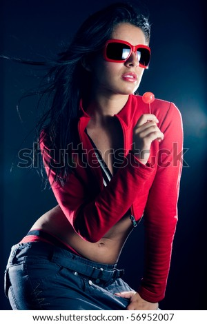 Sexy beautiful dancing hip hop girl with red sunglasses, holding a candy in her hand - stock photo