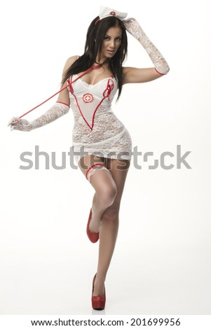 Sexy beautiful female brunette doctor in red shoes and  white stocking and red lips on a white background long hair full length - stock photo