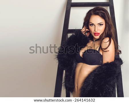 Sexy beautiful nude brunette woman in fur and in bra posing in front of the stairway, looking to the camera. Fashion beauty concept. Bright background with copyspace - stock photo
