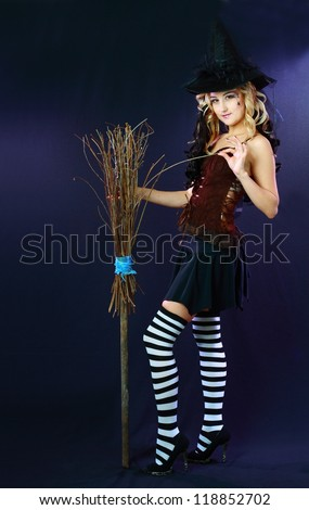 Sexy beautiful witch with broom on dark background - stock photo