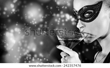 Sexy beautiful woman drinking champagne, posing in carnival mask, looking at camera. - stock photo