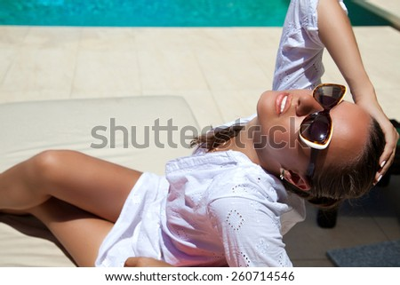 Sexy beautiful woman holding hand behind head, relaxing at the luxury poolside. Girl at travel spa resort pool. Summer luxury vacation. (focus on woman face) - stock photo