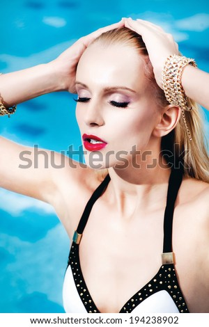 Sexy beautiful woman or girl in swimsuit sunbathing on a lounger by the pool to the sea. Fashion make-up on her face. Half-naked blonde girl in beautiful lingerie resting in the sun - stock photo